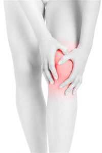 woman holding her painful knee on white background