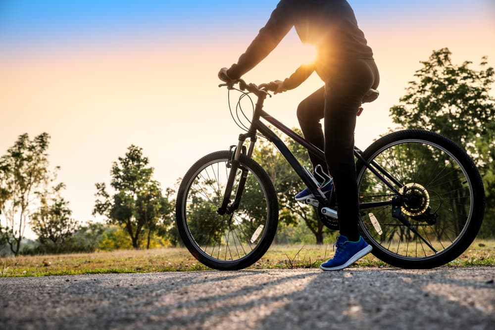 Image of woman early morning with riding bicycle outdoors. Looking a sunlight