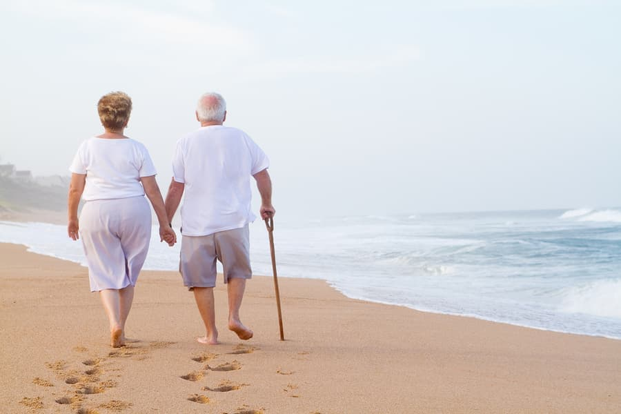 A senior couple walking hand in hand on an empty beach