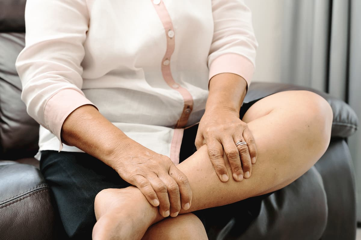 Senior women holding her leg with hands for pain relief