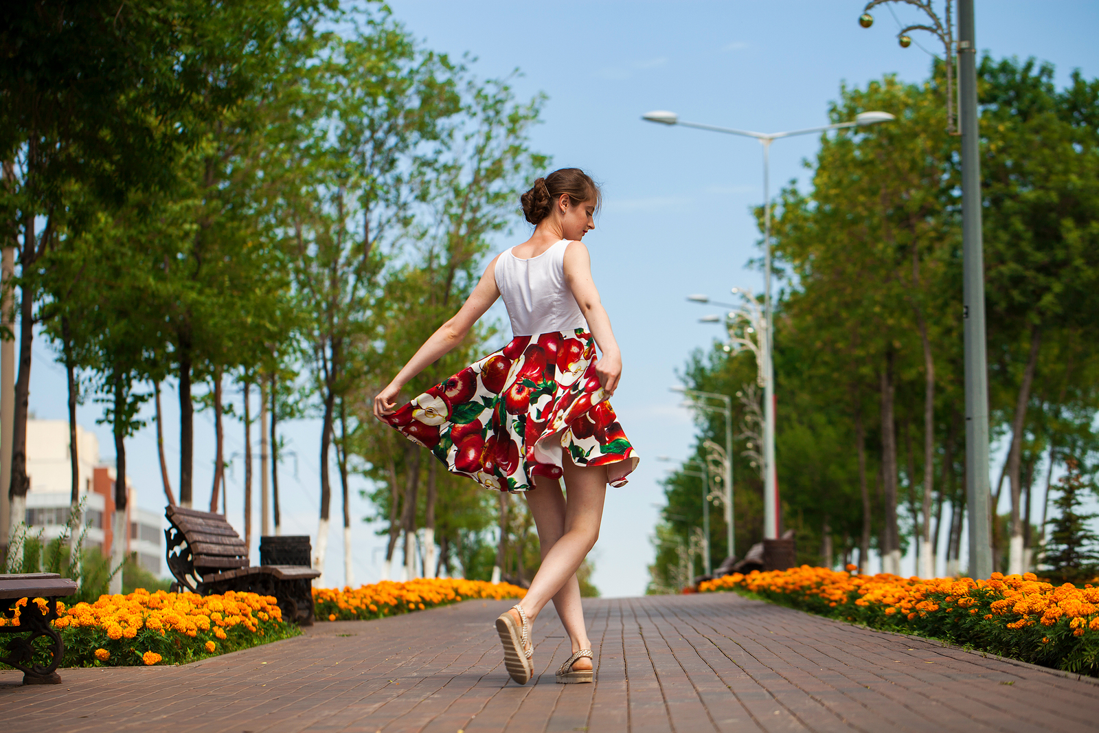 Full body portrait of a young brunette woman walking in flowers dress, summer park outdoors